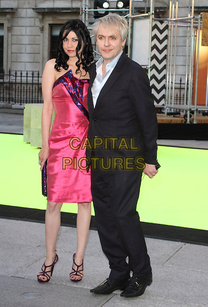 Nefer Suvio; Nick Rhodes<br /> Royal Academy Summer Exhibition 2013 VIP Preview Party at the Royal Academy, Piccadilly, London, England.<br /> June 5th 2013<br /> full length black suit pink silk satin dress couple <br /> CAP/ROS<br /> &copy;Steve Ross/Capital Pictures