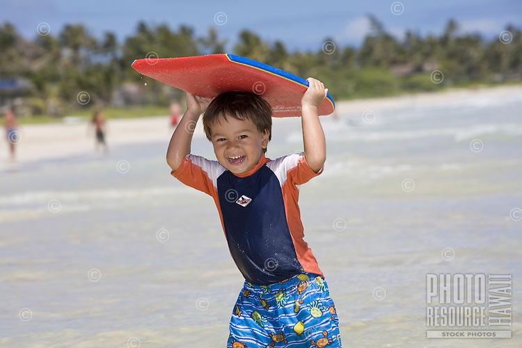A boy holds a body board on top of his head at Kailua Beach, Oahu, Hawaii.
