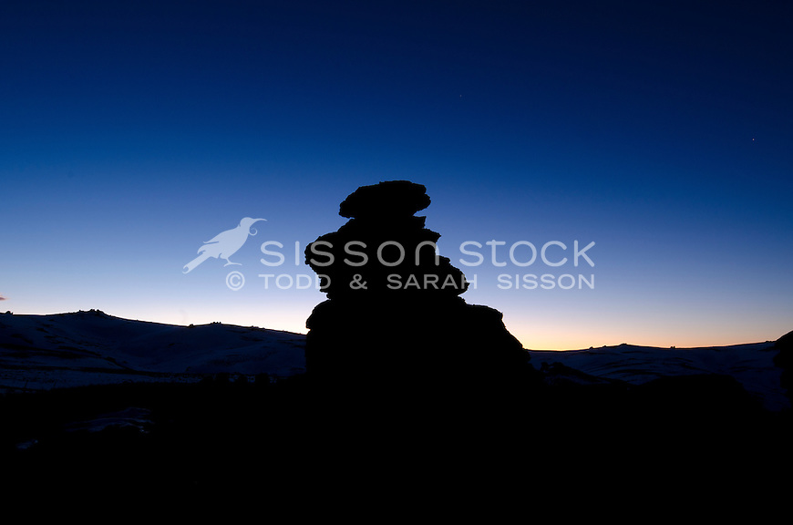 Rocks (Tarn) silhouetted at sunset at the summit of Duffers Saddle on the Nevis Road, Central Otago, New Zealand