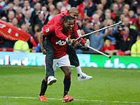 Pictured: Patrice Evra is helping an injured team mate to get to the podium. Sunday 12 May 2013<br /> Re: Barclay's Premier League, Manchester City FC v Swansea City FC at the Old Trafford Stadium, Manchester.