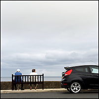 Couple on a bench on the promenade by the sea