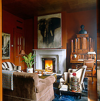 A contemporary painting of an elephant hangs above the marble fireplace in the library