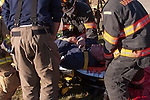 A patient hurt and in pain being put on a stretcher