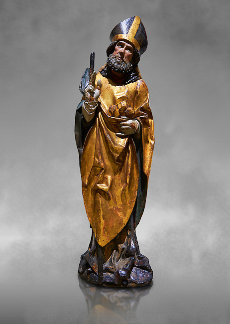 Gothic wooden statue of Sant Nicolau (Nicholas) from Gremany, circa 1500, tempera and gold leaf on wood, from the church of San Miguel de Medina del Campo, Valladolid..  National Museum of Catalan Art, Barcelona, Spain, inv no: MNAC  65507. Against a grey art background.
