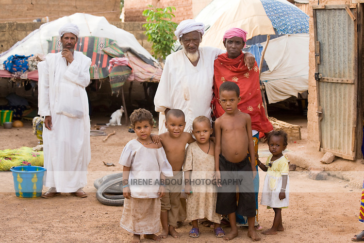 A Touareg family poses for a photo with their Fulani neighbor.  The Tuareg are traditionally nomadic pastoralists.  Here in Ouagadougou, Burkina Faso, the family lives under makeshift tents patched together from pieces of cloth.