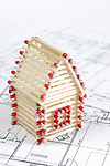House made from matches standing on construction plans Construction industry Home renovation Real estate agency Architectural design concept