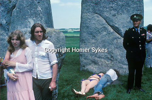1970's Free festival at Stonehenge to celebrate the summer solstice June 21st 1979. Besides the hippies a small group of English tourists watched as others lay in the sun.