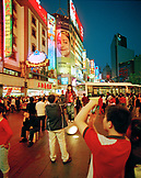 CHINA, Shanghai, people take photos of one another on a busy urban shopping street