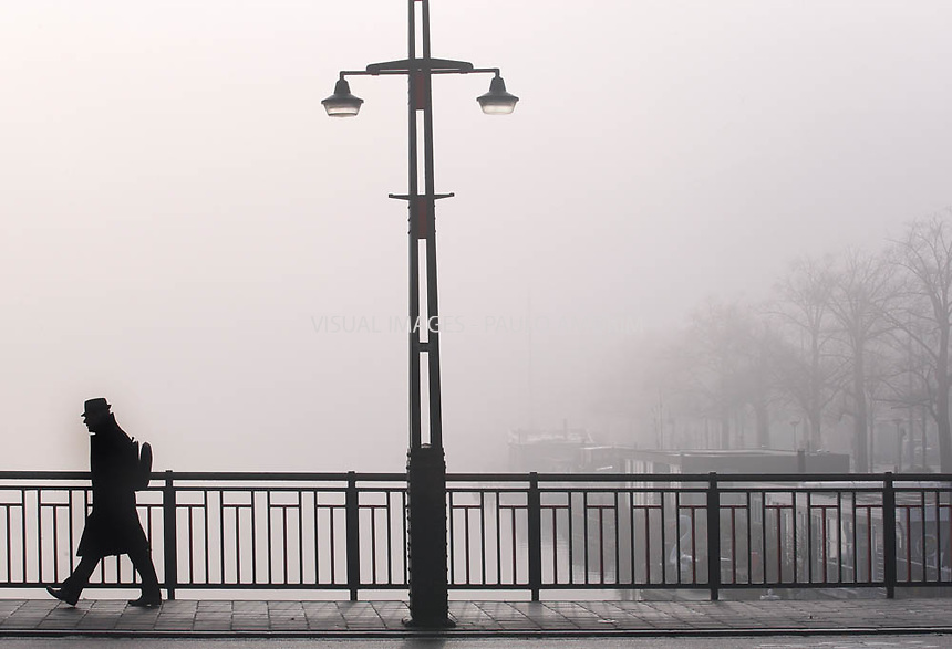 A man walks next Amstel river in Amsterdam suffers from the dense fog on wednesday morning 23 November 2011.