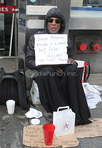 """NEW YORK, NY - APRIL 14:  Homeless man, panhandler and Hillary Clinton supporter spotted holding a sign in Midtown Manhattan which reads 'Good Morning Make it a Great Day Fore """"Hillary"""" The Lady President' in New York, New York on April 14, 2016. Photo Credit: Rainmaker Photo/MediaPunch"""