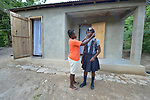 Darima Marie Motte helps her daughter Chedline get ready for school in front of their new home in Lareserve, a village near Jean-Rabel in northwestern Haiti. The family's previous house was destroyed during Hurricane Matthew in 2016, and Church World Service, a member of the ACT Alliance, helped the family build their sturdy new home.