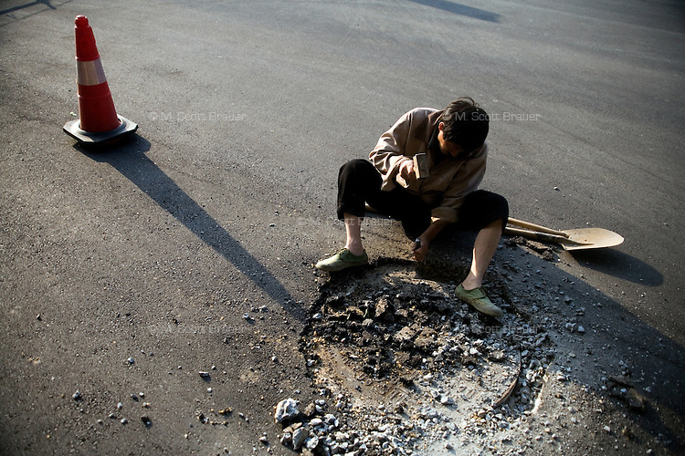 A construction worker removes concrete from a manhole after a road construction project was finished in Nanjing, China.