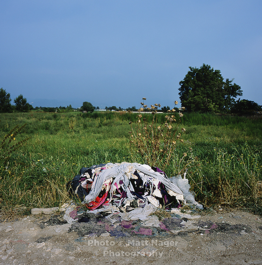 A pile of illegally disposed clothing scraps from a local tailoring company lies abandoned next to a farm near Marigliano, Italy. Piles of urban waste can be found throughout the provinces of Naples and Caserta. Surrounding farms have seen a drop in production quality of produce...PHOTOS/ MATT NAGER