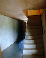 Low maintenance polished concrete floors and plywood ceilings line this stark staircase hall
