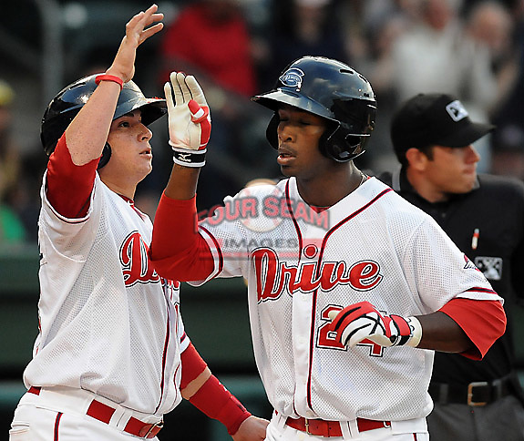 Left fielder Brandon Jacobs (24) of the Greenville Drive, Class A affiliate of the Boston Red Sox, is congratulated by Christian Vazquez (15) after hitting a home run in a game against the Augusta GreenJackets on Opening Day, April 7, 2011, at Fluor Field at the West End in Greenville, S.C. Photo by Tom Priddy / Four Seam Images