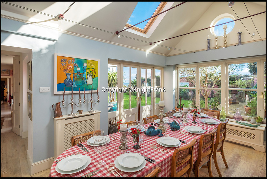 """BNPS.co.uk (01202 558833)<br /> Pic: KnightFrank/BNPS<br /> <br /> The dining room.<br /> <br /> This quaint beach hut is the perfect spot for those dreaming of living by the sea - and you also get a seven-bedroom house for the £2.24million price tag.<br /> <br /> Ledge House on the Isle of Wight is one of very few properties on the island that has direct access to the beach and the house and gardens take full advantage of the breathtaking views.<br /> <br /> While the house itself is impressive, with more than 4,000 sq ft of living space and beautiful gardens, the Boat House and Beach Hut set down by the beach are the real selling point. <br /> <br /> Owner Georgie Donnelly described them as being like """"another world"""", completely secluded from the main house and above prying eyes from the beach."""