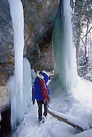 An ice climber adjusts a load of ropes as he hikes between ice formations hanging from cliffs in Pictured Rocks National Lakeshore near Munising, Mich.