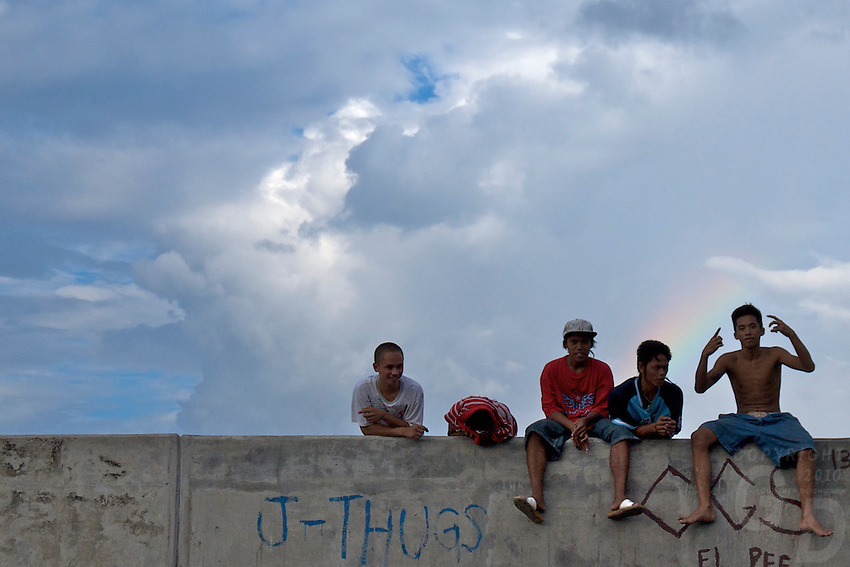 Teenage Gang on a wall slum area of Manila, view from the car window Manila, Philippines