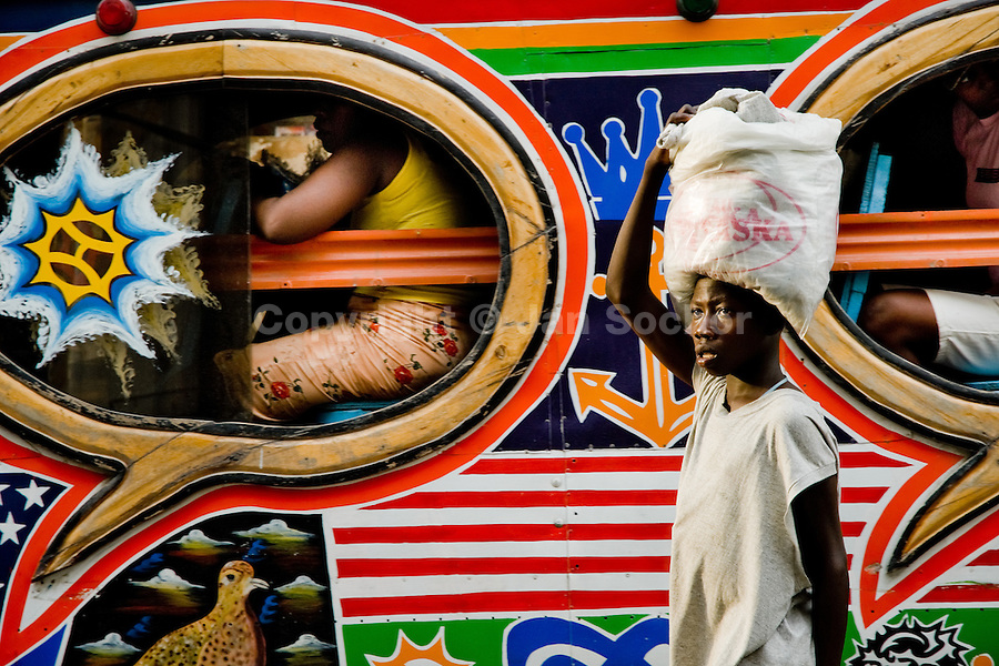 A Haitian street vendor offers water to the tap-tap passengers on the street of Port-au-Prince, Haiti, 26 July 2008. Tap-tap vehicles serve as public transportation in Haiti. They are private, operate over fixed routes, departing only when full. Tap-taps are decorated with bright and shiny colors and with a lot of fancy designed elements. There are scenes from the Bible, Christian slogans, TV stars or famous football players often painted on a tap-tap body. Tap-tap name comes from sound of taps on the metal bus body signifying a passenger's request to be dropped off.