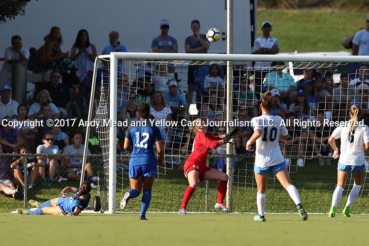 CARY, NC - AUGUST 18: Duke's Taylor Racioppi (7) scores a goal over North Carolina's Samantha Leshnak (13). The University of North Carolina Tar Heels hosted the Duke University Blue Devils on August 18, 2017, at Koka Booth Stadium in Cary, NC in a Division I college soccer game.