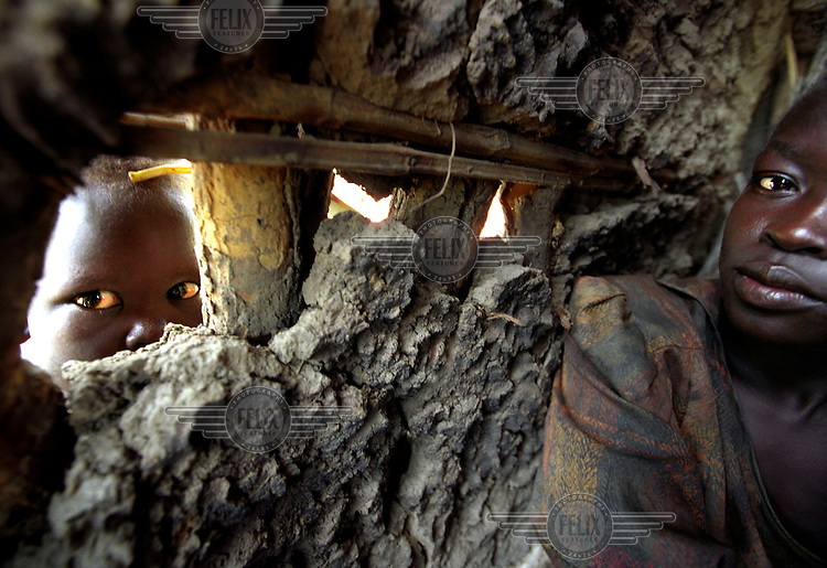 A child looks through a hole in the wall of a hut built of wood and mud..