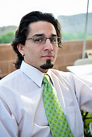 A 30 year-old Hispanic man with a goatee, wearing glasses and a white dress shirt with a green necktie at an outdoor, afternoon picnic in Penrose, Colorado, United States, North America.