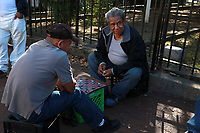 (161029RREI2979) Esquineros playing damas (checkers).Annual neighborhood Day of the Dead commemoration. About 25 people and musicians processed down Mt. Pleasant St. NW, led by the Mexican group Son Cosita Seria. The event has been organized by Quique Aviles, who was absent this year because his mother passed away Wednesday in El Salvador. Washington DC Oct. 29, 2016 . ©  Rick Reinhard  2016     email   rick@rickreinhard.com