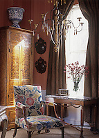 A metal chandelier hangs above an armchair upholstered in a floral fabric. A flower arrangement stands on a side table nearby.