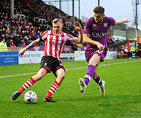 Lincoln City's Harry Anderson crosses under pressure from Carlisle United's Macaulay Gillesphey<br /> <br /> Photographer Andrew Vaughan/CameraSport<br /> <br /> The Emirates FA Cup Second Round - Lincoln City v Carlisle United - Saturday 1st December 2018 - Sincil Bank - Lincoln<br />  <br /> World Copyright © 2018 CameraSport. All rights reserved. 43 Linden Ave. Countesthorpe. Leicester. England. LE8 5PG - Tel: +44 (0) 116 277 4147 - admin@camerasport.com - www.camerasport.com