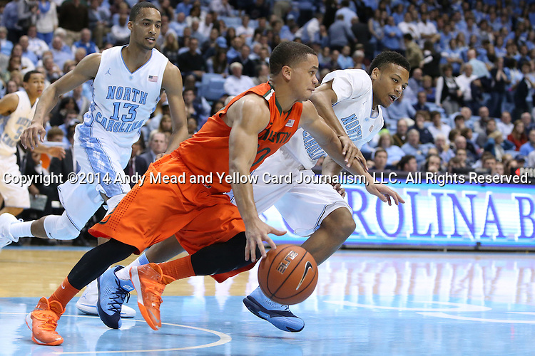 08 January 2014: Miami's Manu Lecomte (BEL) (in orange) is chased and fouled by North Carolina's Nate Britt (right). The University of North Carolina Tar Heels played the University of Miami Hurricanes in an NCAA Division I Men's basketball game at the Dean E. Smith Center in Chapel Hill, North Carolina. Miami won the game 63-57.