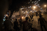In this Monday, Jul. 15, 2013 photo, anti- Morsi protesters throw stones to the supporters of the ousted president Mohammed Morsi as clashed erupted between them during night in the nearby streets of Ramses bridge in Cairo, Egypt. (Photo/Narciso Contreras).