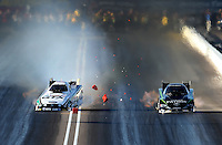 Feb. 22, 2013; Chandler, AZ, USA; NHRA funny car driver John Force (left) crosses the centerline taking out the timing blocks alongside Alexis DeJoria during qualifying for the Arizona Nationals at Firebird International Raceway. Mandatory Credit: Mark J. Rebilas-
