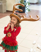 STAFF PHOTO ANTHONY REYES &bull; @NWATONYR<br /> Saige Prim, 6, of Bentonville, laughs as teammates try to toss a ring on her antlers Friday, Dec. 5, 2014 during the Arkansas Virtual Academy's winter party at the Jones Center in Springdale. The event featured a number of games, crafts and a gingerbread house competition with prizes going to the winners in different age categories.