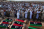 Men gather at a funeral to pray over eight bodies found last week in a mass grave near the town of Al-Qala in the Nefusa Moutains, Libya, Friday, Sept. 30, 2011. The eight were reburied next to 35 bodies found in a separate mass grave in the area. Members of the Amazigh indigenous tribe, the men were arrested from their homes and at checkpoints by pro-Gaddafi forces, imprisoned, and finally executed sometime in June. The men, many of them related as fathers and sons, or as brothers, were missing until the first, larger mass grave was found in mid-August.