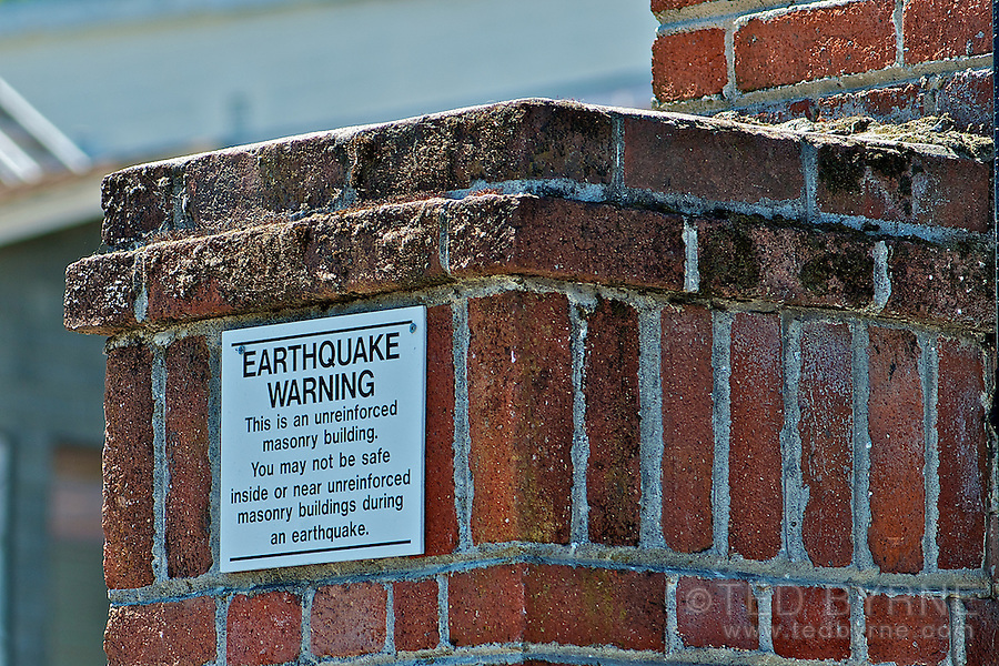 Earthquake warning sign on brick building
