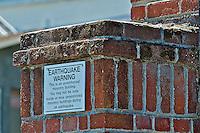 Earthquake warning sign on brick building