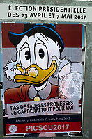 France. Ile de France. Paris. Political opponents have glued a Balthazar Picsou ( in english Scrooge McDuck) poster on an official campaign poster of a French presidential election candidate. Scrooge McDuck is a fictional character created in 1947  for The Walt Disney Company. Scrooge is an elderly Scottish anthropomorphic Pekin duck with a yellow-orange bill, legs, and feet. He typically wears a red or blue frock coat, top hat, pince-nez glasses, and spats. <br /> 22.04.17 &copy; 2017 Didier Ruef