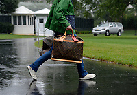 A White House aide carries Louis Vuitton bags prior to United States President Donald J. Trump and first lady Melania Trump's departure from the White House September 2, 2017 in Washington, DC. <br /> Credit: Olivier Douliery / Pool via CNP /MediaPunch