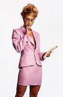 Photo of a secretarty in a pink skirt suit looking at the boss with a pad in her hand and a pen in her mouth.