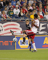 New England Revolution forward Zak Boggs (33) crosses the ball as New York Red Bulls defender Roy Miller (7) defends. The New England Revolution defeated the New York Red Bulls, 3-2, at Gillette Stadium on May 29, 2010.