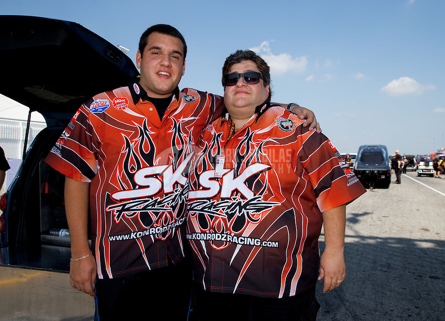 Aug. 30, 2013; Clermont, IN, USA: Stefan Kontos (left) and father Spiro Kontos owner of the car driven by NHRA top alcohol funny car driver Cassie Simonton during qualifying for the US Nationals at Lucas Oil Raceway. Mandatory Credit: Mark J. Rebilas-USA TODAY Sports