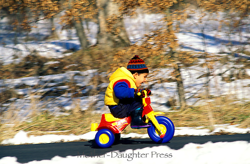 Young boy tries his new Christmas tricycle with exuberance and delight