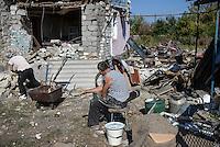 Man observes remains of his house destroyed by shelling in Novosvetlovka, Ukraine.
