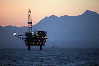 Oil and natural gas production platforms stand in Cook Inlet, offshore from Nikiski, Alaska, as the sun sets behind Mount Spurr volcano and other peaks in the Alaska Range. Oil and natural gas are an important contributor to the Kenai Peninsula's economy.