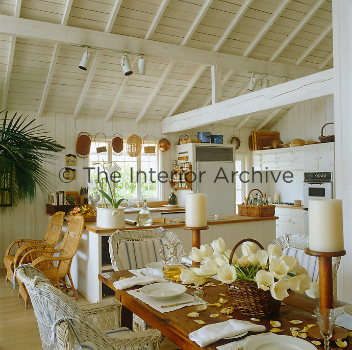 In an open-plan kitchen-diner the white-painted ceiling beams and walls create an atmosphere of cool tranquillity