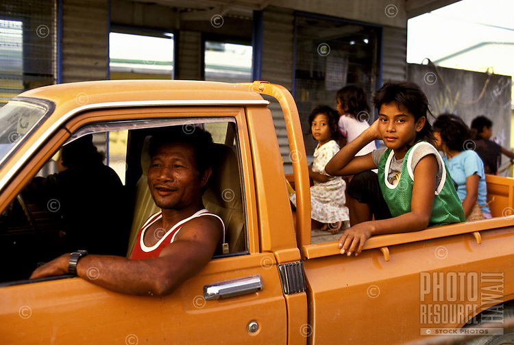 Young girls in back of an orange pick-up truck being driven by an adult male, Yap, Micronesia.