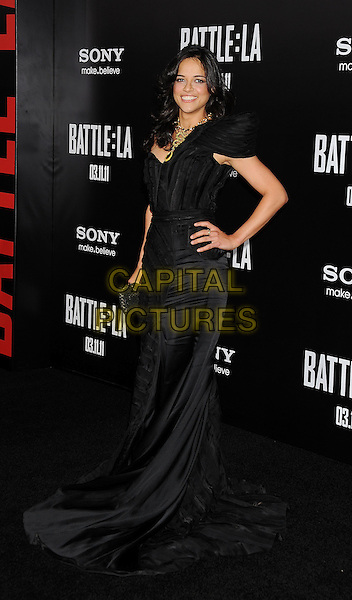 "MICHELLE RODRIGUEZ.Angeles premiere of ""Battle: Los Angeles"" at the  Regency Village Theatre in Westwood, California, USA..March 8th, 2011.full length black one shoulder dress fishtail hand on hip  .CAP/ROT/TM.© TM/Roth/Capital Pictures"