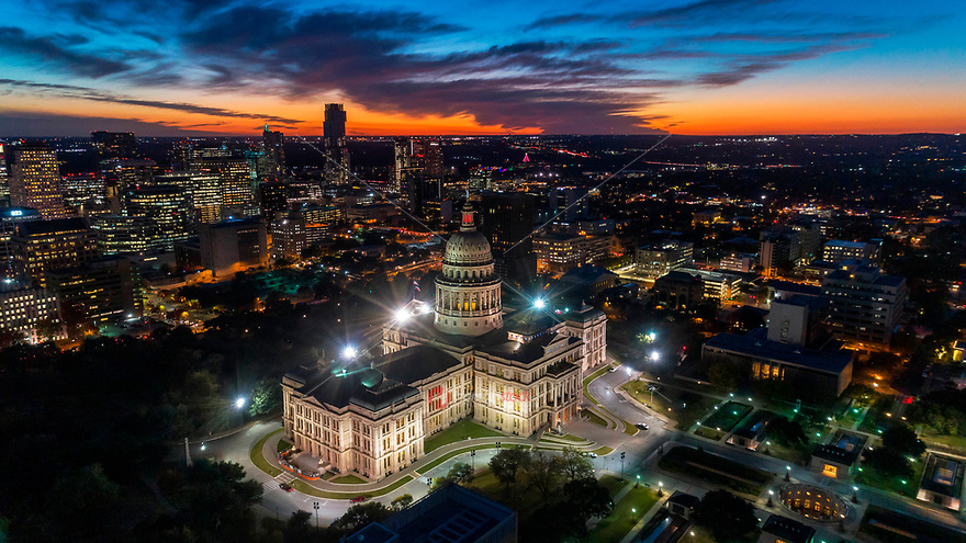Aerial image of vibrant orange and soft blues in a dramatic sky surround the Texas State Capitol building during this spectacular sunset over downtown Austin, Texas. The Zilker Holiday Tree and Austin Trail of Lights can be seen in the distant background.