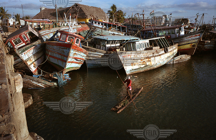 A fisherman ekes out a living in Nagappattinam, on the southeastern coast of India. Behind him are boats smashed by the tsunami. The December 26, 2004 tsunami killed thousands of people along this coast, smashing boats, roads and houses, and devastating the lives of countless families..