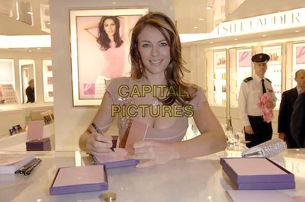 ELIZABETH HURLEY.makes a personal appearance at Harrods to sign the Estee Lauder Pink Ribbon Diary as part of Breast Cancer Awareness Month and also to officially open the brand new Estee Lauder counter in the Beauty Apothecary, Harrods, Knightsbridge, England, UK,.19th October 2006..Liz half length beige sitting silver cross necklace pen signing cleavage smiling  .CAP/FIN.©Steve Finn/Capital Pictures.